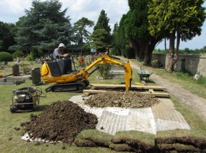 A man digging a grave with a backhoe